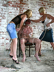 Busty bitches torture a naked guy tied to a chair in an abandoned farm